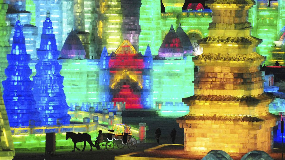 A horse carriage carrying tourists travels past ice sculptures during the lights testing period of the 13th Harbin Ice and Snow World in Harbin, Heilongjiang province in China on December 25, 2011. The Harbin International Ice and Snow Festival will be officially launched on January 5, 2012.