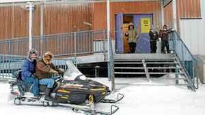 Residents arrive by snowmobile to cast their ballots in the federal election at the arena in Clyde River, Nunavut, on the east coast of Baffin Island, Tuesday, Oct.14, 2008.