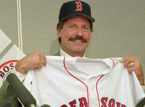 File: Boton Red Sox Kevin Kennedy holds up his jersey during a news conference in Boston Tuesday, Oct. 18, 1994. Kennedy made a speedy return to managing Tuesday when he was hired by the Red Sox six days after losing his job with the Texas Rangers. (AP Photo/Susan Walsh)