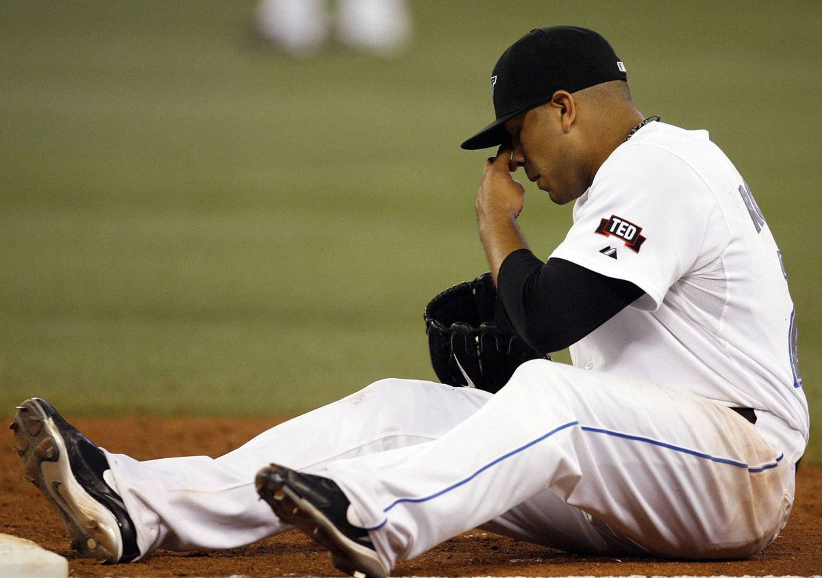 Toronto Blue Jays pitcher Ricky Romero sits behind first base after he fell trying to get the out against New York Yankees batter Hideki Matsui during the fifth inning of their MLB American League baseball game in Toronto September 3, 2009. REUTERS/ Mike Cassese (CANADA SPORT BASEBALL)