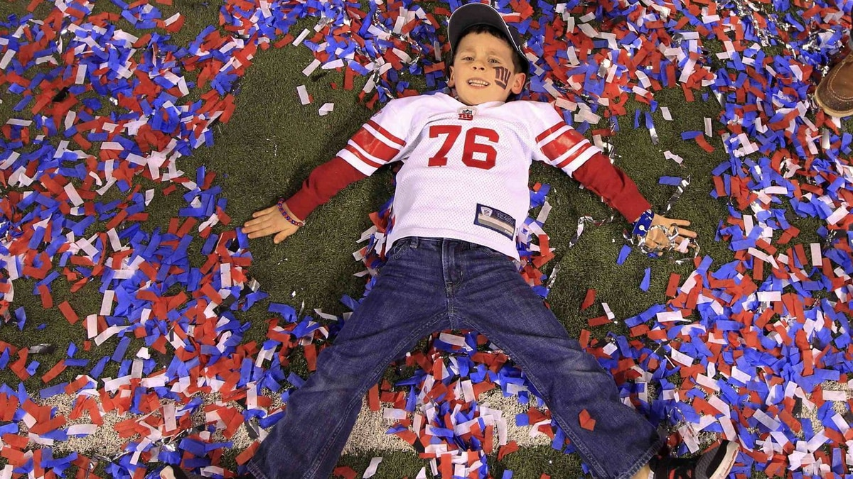 The son of New York Giants guard Chris Snee makes confetti angels after the Giants defeated the New England Patriots in the NFL Super Bowl XLVI football game in Indianapolis, Indiana, February 5, 2012. REUTERS/Lucy Nicholson