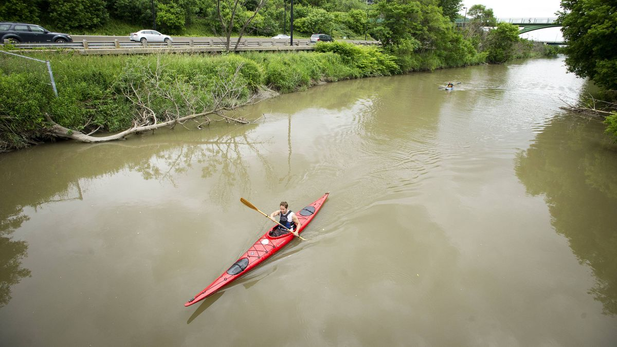 Kayakers paddle down the the lower Don River as traffic on the Don Valley Parkway speeds by in Toronto, Ont. June 26, 2011.