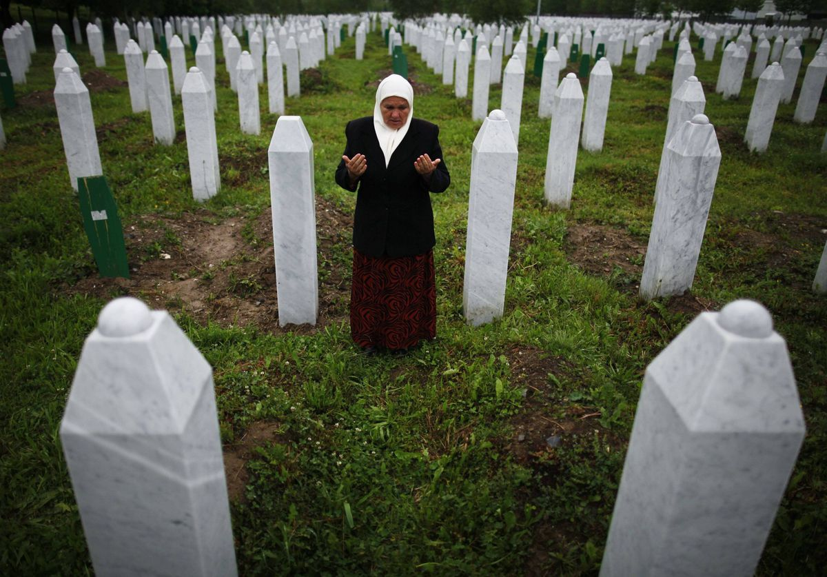Mejra Dzogaz prays near the graves of her two sons before the television broadcast of the court proceedings of former Bosnian Serb general Ratko Mladic's in Potocari, near Srebrenica. Mejra's husband, three sons and a grandson were killed during the Srebrenica massacre in 1995 by a Serbian army unit commanded by Mladic.