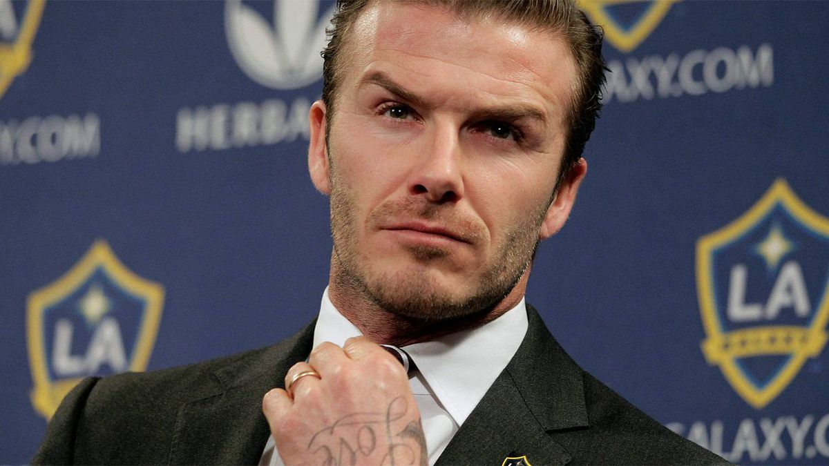 Los Angeles Galaxy's David Beckham fixes his tie during a soccer news conference in Los Angeles, Thursday, Jan. 19, 2012.