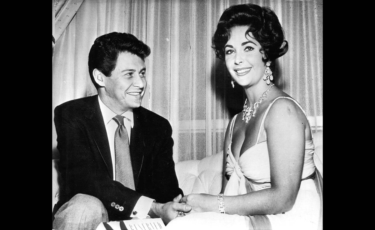 Elizabeth Taylor and Eddie Fisher hold hands as they disclose plans to wed.