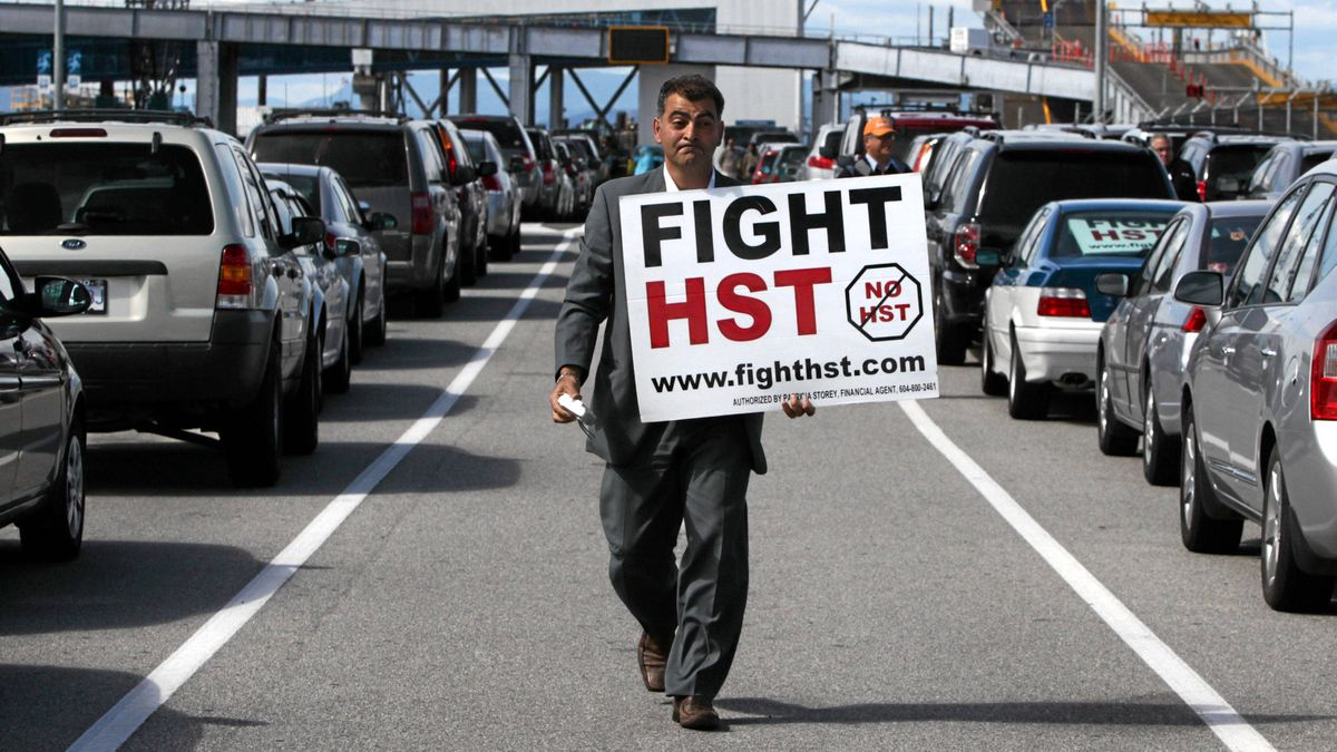 Local anti-HST organizer Eddie Petrossian carries a sign as he walks to meet former British Columbia premier Bill Vander Zalm before boarding a ferry in Tsawwassen, B.C., on Wednesday June 30, 2010, to deliver anti-HST petitions which contain more than 700,000 signatures to Elections B.C. in Victoria.