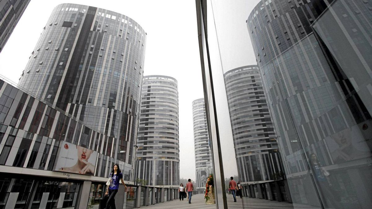 People walk along the Sanlitun SOHO residential and commercial complex in Beijing.