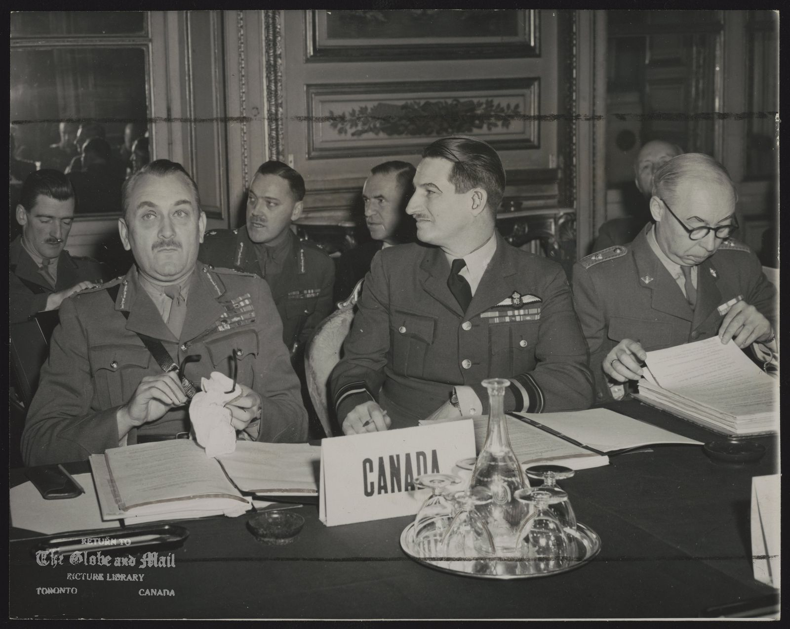 NORTH ATLANTIC TREATY ORGANIZATION (NATO) CANADA AT ATLANTIC PACT TALKS ---Canadian delegates to the Atlantic Pact military conference in Paris are seen at table and behind others in the French Navy Department building. From left: Chief of Staff Lt.-Gen. Charles Foulkes, Canadian Army Chief of Staff: Air Vice-Marshal Hugh Campbell, Canadian representative to the standing Atlantic Pact defense group, and (at back, left) Brig. J. D. B. Smith. At extreme right is Lt.-Gen. E. Goertz, Danish Army commander-in-chief.