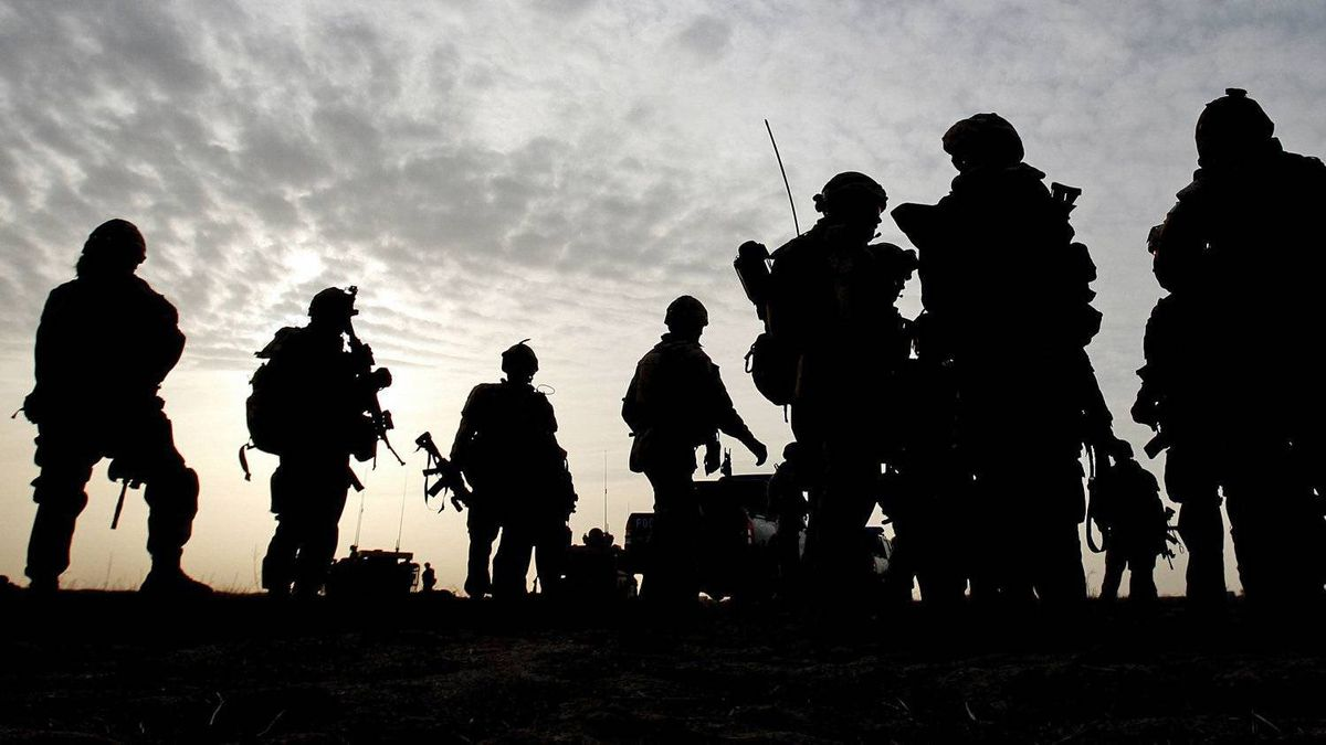 Canadian soldiers are silhouetted during a village search and security operation in the Dand area of Kandahar Province, southern Afghanistan, on Jan. 26, 2010.
