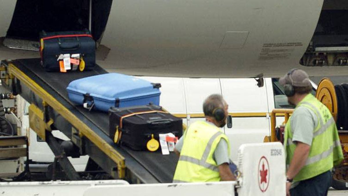 Baggage handlers unload an Air Canada flight at Toronto Pearson International Airport.