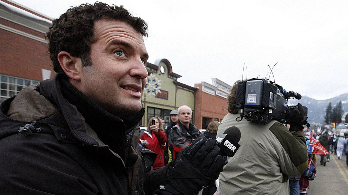 Rick Mercer watches the torch go by in Rossland, British Columbia, Canada while taping segments for the Rick Mercer Report during the town's winter carnival, which was moved to coincide with the arrival of the Vancouver 2010 Olympic Torch Relay.