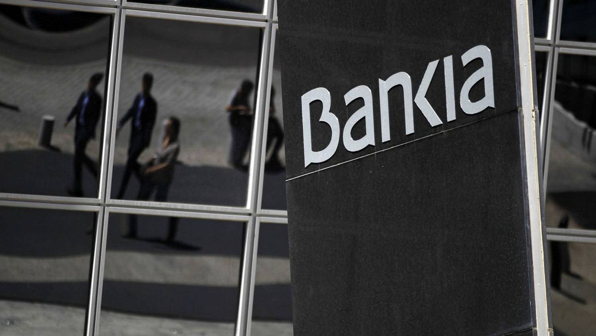 People are reflected on the wall of Bankia headquarters building in Madrid, May 9, 2012. The Spanish government has converted Bankia's debt into equity and will have a controlling stake in the bank.