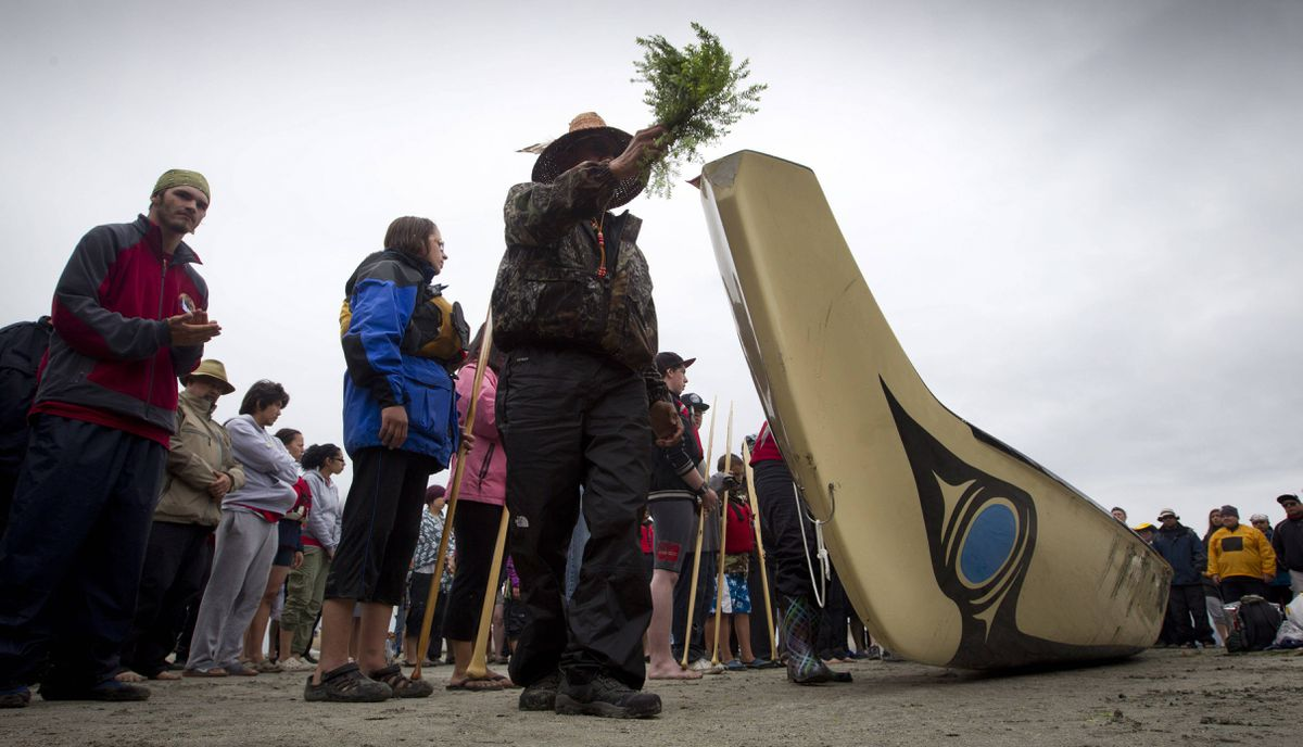 A canoeists from the Pulling Together journey blesses a canoe during a prayer circle before leaving for the Ahousat, B.C. first nation.