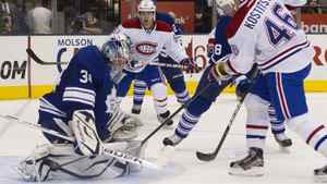 Toronto Maple Leafs goaltender James Reimer (left) saves as shot from Montreal Canadiens' Andrei Kostitsyn (right) during first period NHL hockey action in Toronto on Thursday October 6, 2011.