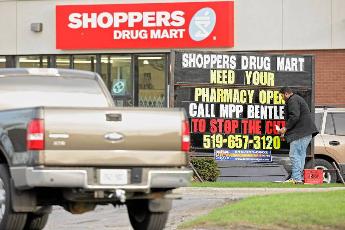 A protest sign is installed in front of a Shoppers Drug Mart in the west end of London, Ont., challenging the recent provincial government decision on generic drug pricing.