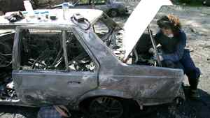 A criminology graduate student checks over a car that has been torched to track evidence at the Justice Institute of B.C. Aug 23, 2006.