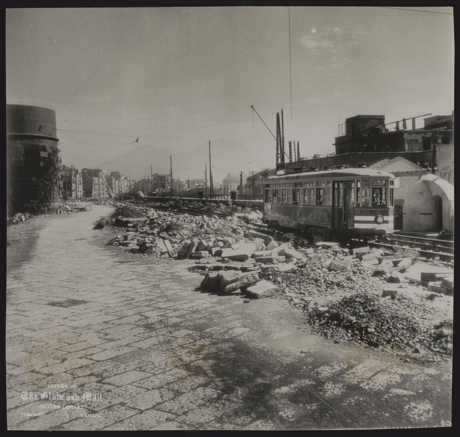 NAPLES city (Italy) (NY15-OCT.12)-NO POWER---DEBRIS LITTERED TRACKS AND NO POWER KEEP THIS STREET CAR STATIONARY IN RAVAGED NAPLES, ITALY, GERMANS MINED OR BOMBED EVERY IMPORTANT PUBLIC BUILDING BEFORE EVACUATING THE CITY. (AP WirePhoto) AJB3095L-PL) 43