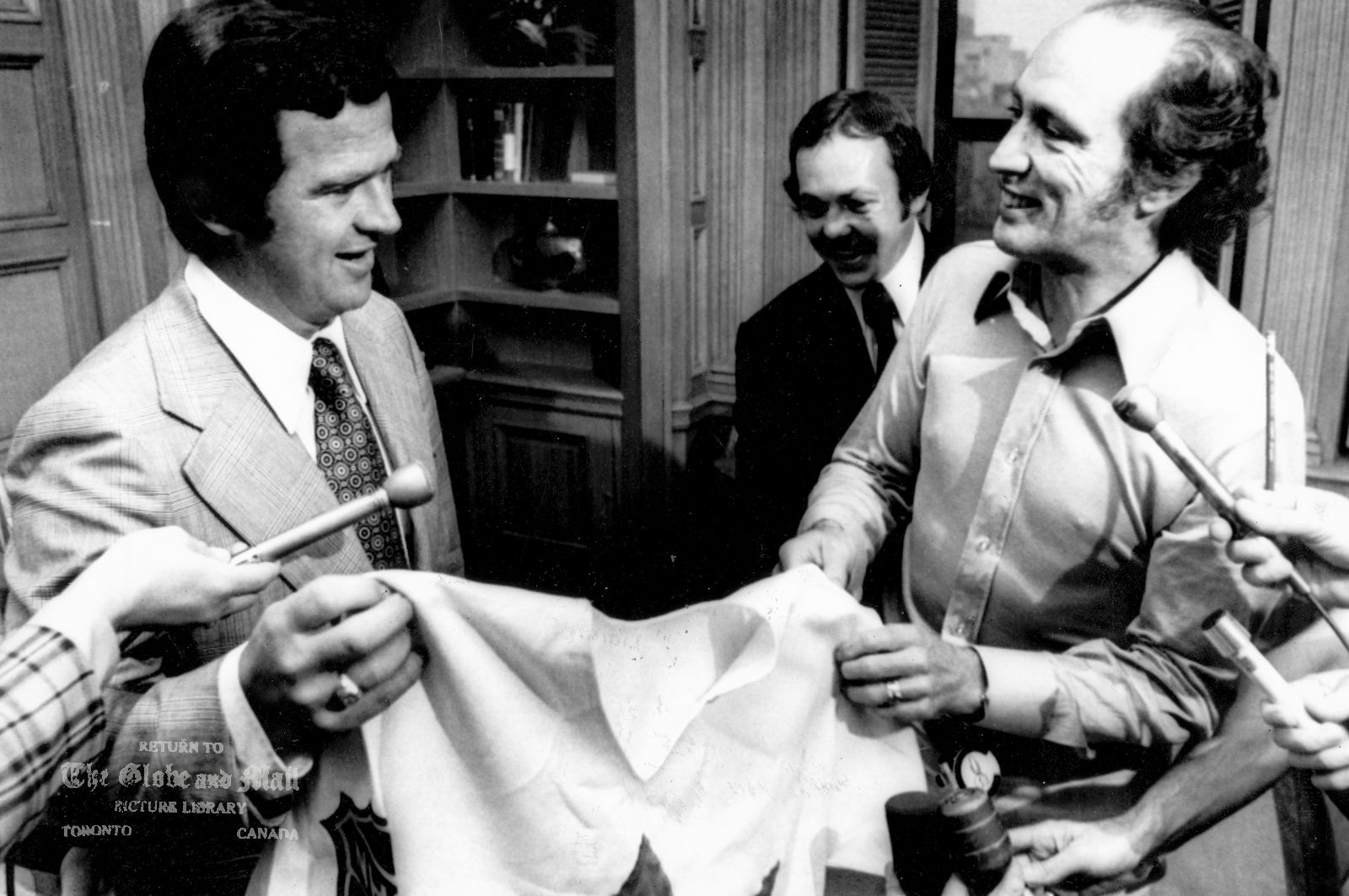 The notes transcribed from the back of this photograph are as follows: JULY 13, 1972 -- OTTAWA -- WELCOME TO THE TEAM -- Prime Minister Pierre Trudeau accepts a Team Canada jersey from manager-coach Harry Sinden at a meeting on Parliament Hill, Thursday, July 13, 1972. Team member Yvan Cournoyer of the Montreal Canadiens looks on. The team, comprised of NHL hockey players will compete in an eight-game series against the Russian national team beginning Sept. 2, 1972 in Montreal. CP PHOTO Originally published July 14, 1972.