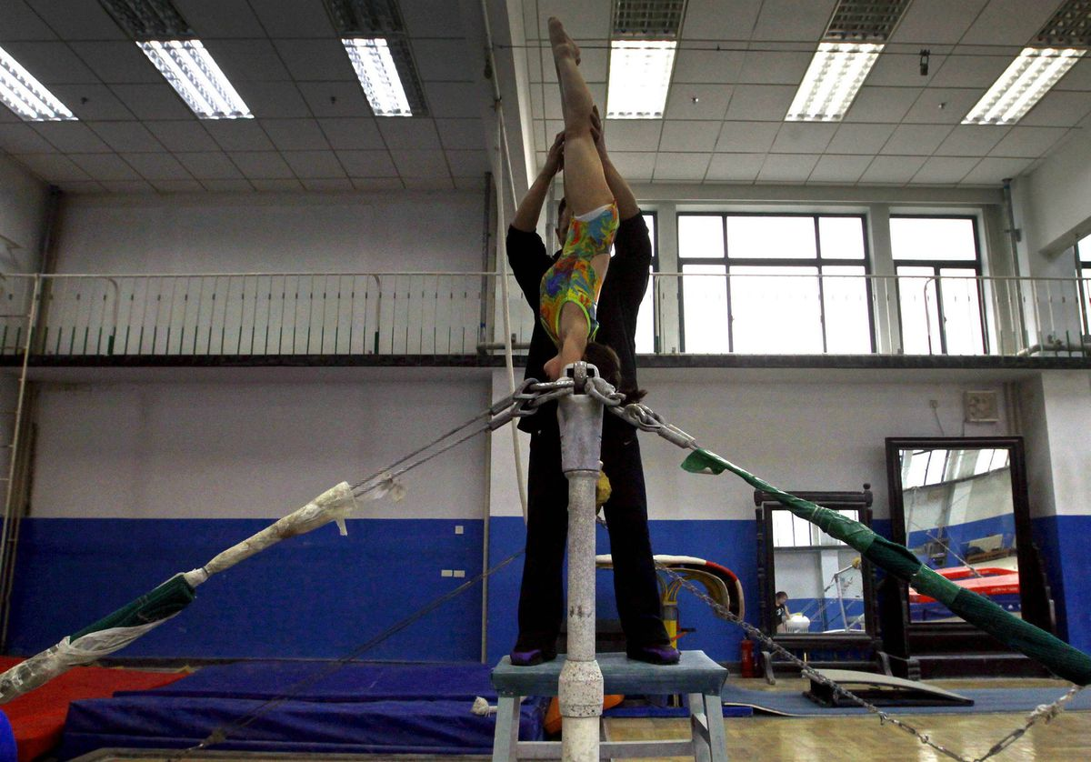 A coach holds onto a young gymnast during a gymnastics class for children.