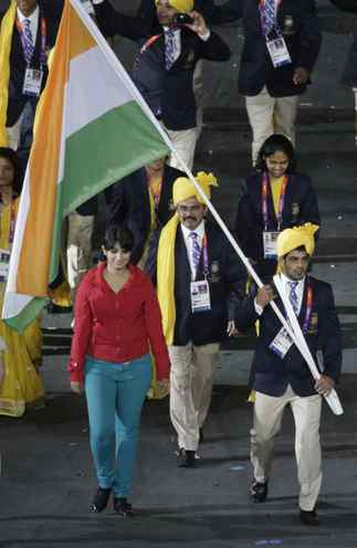India's flag bearer Sushil Kumar holds the national flag as he leads the contingent in the athletes parade during the opening ceremony of the London 2012 Olympic Games at the Olympic Stadium July 27, 2012. A mystery woman gatecrashed India's march past at the Olympic opening ceremony and the delegation are seeking an apology from the London organisers, an Indian newspaper reported on Sunday. Photographs show a woman in red and blue walking close to Kumar on Friday night, in complete contrast to female members of the contingent who were wearing yellow sarees and blue blazers.