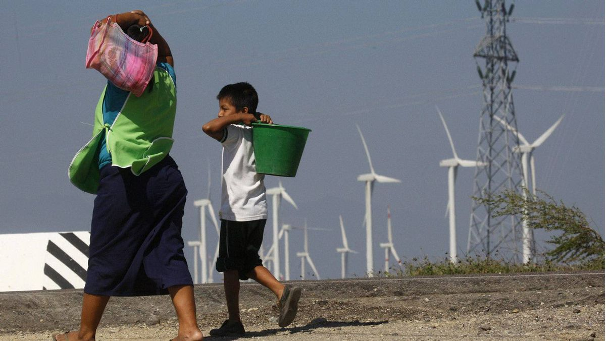 """A woman and a boy walk past wind turbines and an electricity tower in La Ventosa Feb. 7, 2012. Surrounded by towering turbines in every direction, the town of La Ventosa - which means """"the windy place"""" in Spanish - is at the heart of a wind power boom in the country. REUTERS/Jorge Luis Plata"""