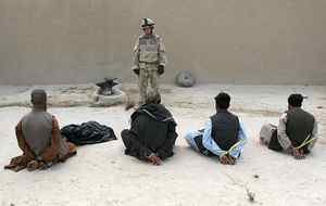 A Canadian soldier guards six of ten suspected Taliban prisoners captured in a raid on a compound in northern Kandahar province on May 10, 2006.