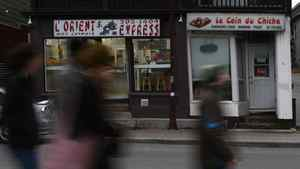 A group of pedestrians walk pass two ethnic restaurants in Gatineau, Quebec.