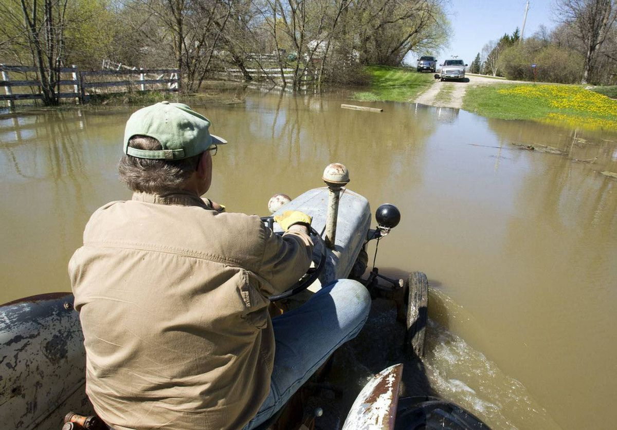 Robin Carter drives his tractor beside his home along the intentional breach of the dike along the Assiniboine River Monday in Manitoba.