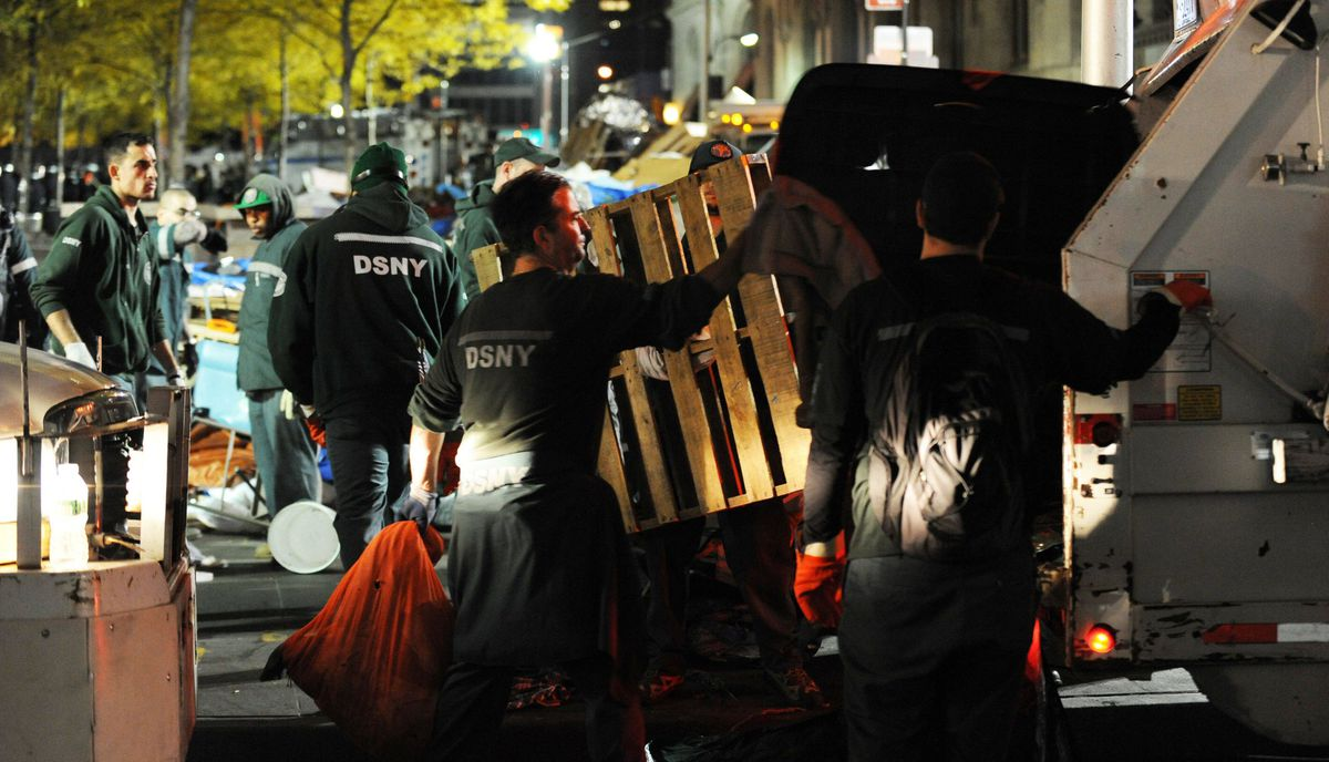 New York City sanitation workers clean up after the 'Occupy Wall Street' protest were evicted from Zuccotti Park in the early morning hours of November 15, 2011 in New York.