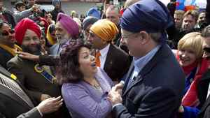 Prime Minister Stephen Harper and his wife Laureen (behind) are mobbed by supporters as they attend the Vaisakhi festival in Vancouver, BC on Saturday April 16, 2011.