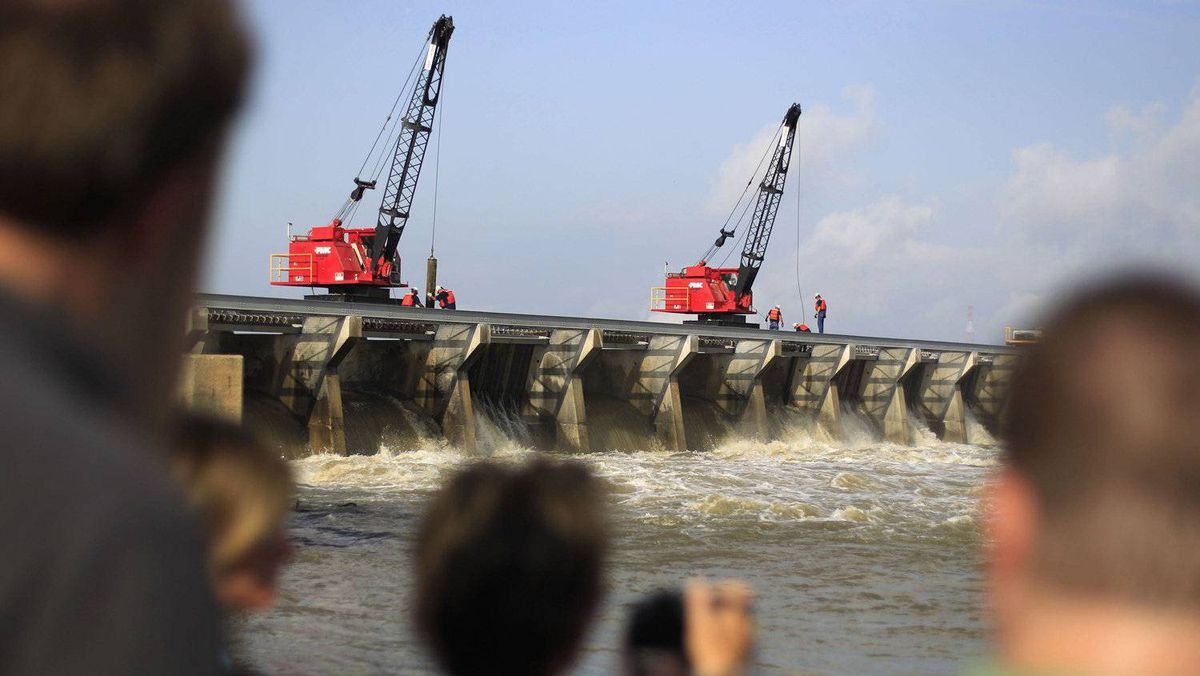 People watch members of the U.S. Army Corps of Engineers opening up bays along the Mississippi River to the Bonnet Carre spillway in Norco, Louisiana May 9, 2011. Officials opened the spillway to send Mississippi River water to Lake Pontchartrain. ENVIRONMENT)