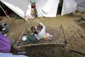 An elderly flood survivor sits with a child in a camp set up for displaced people in Nowshera, Pakistan on Tuesday, Aug. 24, 2010. Recovering from the devastating floods still battering Pakistan will take at least three years, the president said, as the waters swept south after leaving millions homeless and submerging millions of acres of farmland.