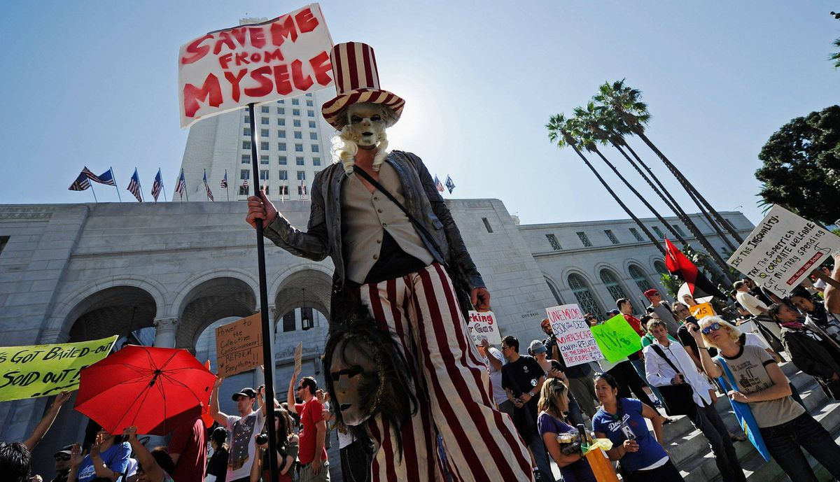 """Protesters hold signs after a march to Los Angeles City Hall during the """"Occupy Los Angeles"""" demonstration in solidarity with the ongoing """"Occupy Wall Street"""" protest in New York City."""