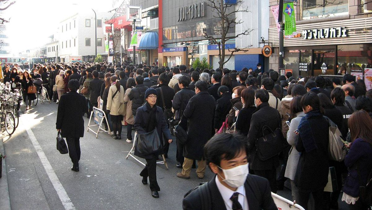"""Commuters queue for a train at the Akihabara JR station in downtown Tokyo as only minimal service is maintained, on March 14, 2011. With ports, airports, highways and manufacturing plants shut down after the March 11 monster earthquake, the Japanese government predicted """"considerable impact on a wide range of our country's economic activities""""."""