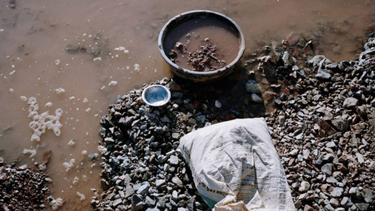 An artisan miner uses mercury to extract gold deposits from rock crushed by hand.