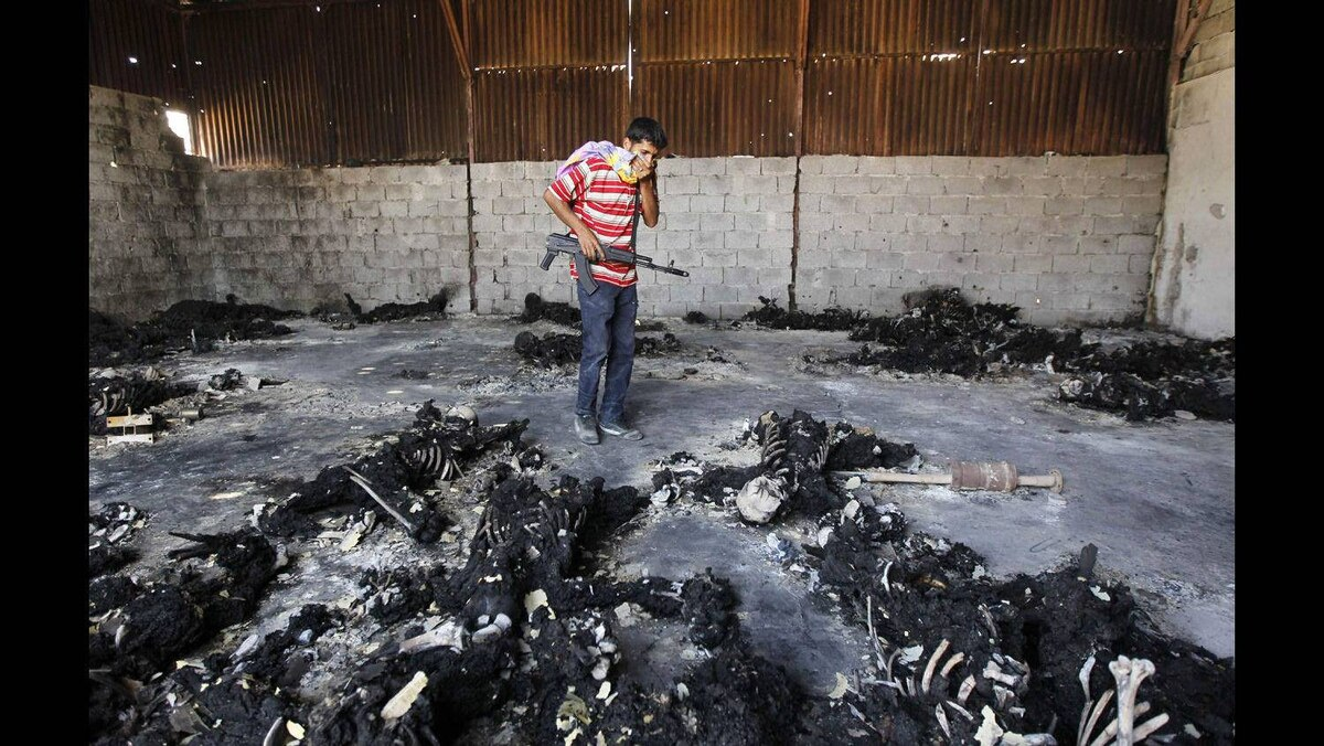 A rebel fighter looks at burnt bodies at a military encampment in southern Tripoli August 28, 2011. The charred remains of around 53 people have been found in a warehouse in the Libyan capital Tripoli, apparently opponents of Muammar Gaddafi who were executed as his rule collapsed, Britain's Sky News reported on Saturday.