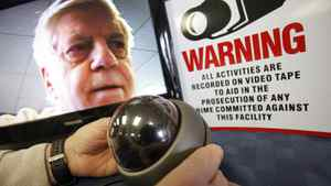 Russell Patterson (face in monitor) adjusts a surveillance camera in his Winnipeg store on Jan. 25, 2012.