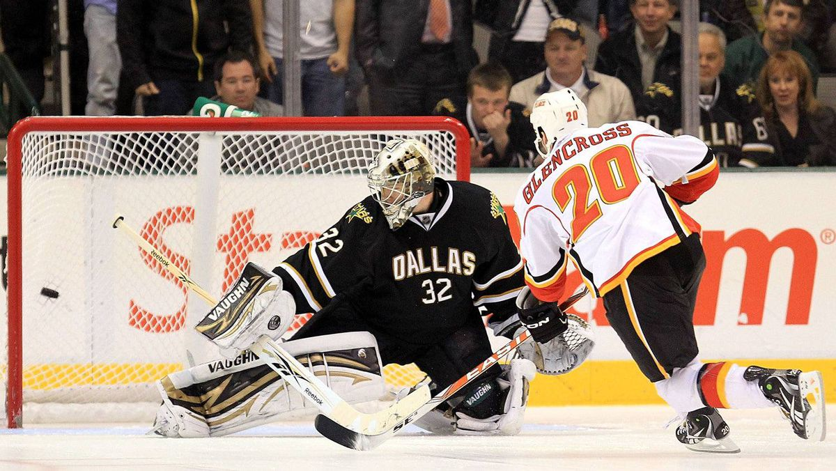 Left wing Curtis Glencross of the Calgary Flames scores the game winning goal in the shootout against Kari Lehtonen of the Dallas Stars at American Airlines Center on March 9, 2011 in Dallas, Texas.