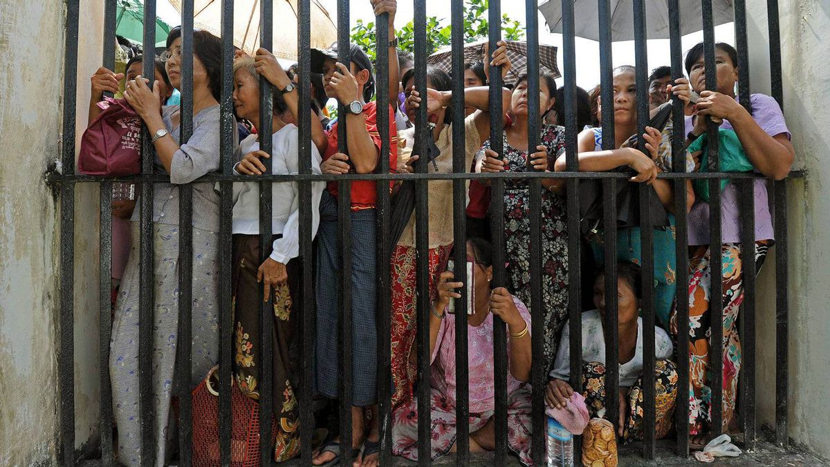 Family members of prisoners wait for their release outside the Insein central prison in Yangon on October 12, 2011.