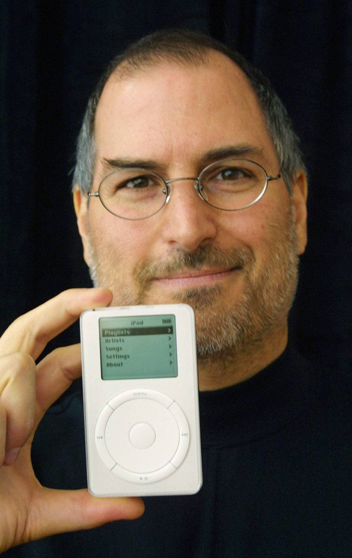 Apple Computer CEO Steve Jobs holds up the new Apple release in Cupertino, California October 23, 2001. The new MP3 music player packs up to 1,000 CD-quality songs into an ultra-portable, 6.5 ounce design that fits in your pocket.
