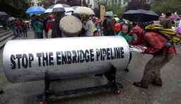Protestors load a giant piece of pipeline with their placards following a protest outside the Vancouver Art Gallery in downtown Vancouver, Tuesday, August 31, 2010. The pipeline was brought there by opponents of the Northern Gateway Pipeline Project which would see a gas pipeline built in northern B.C.