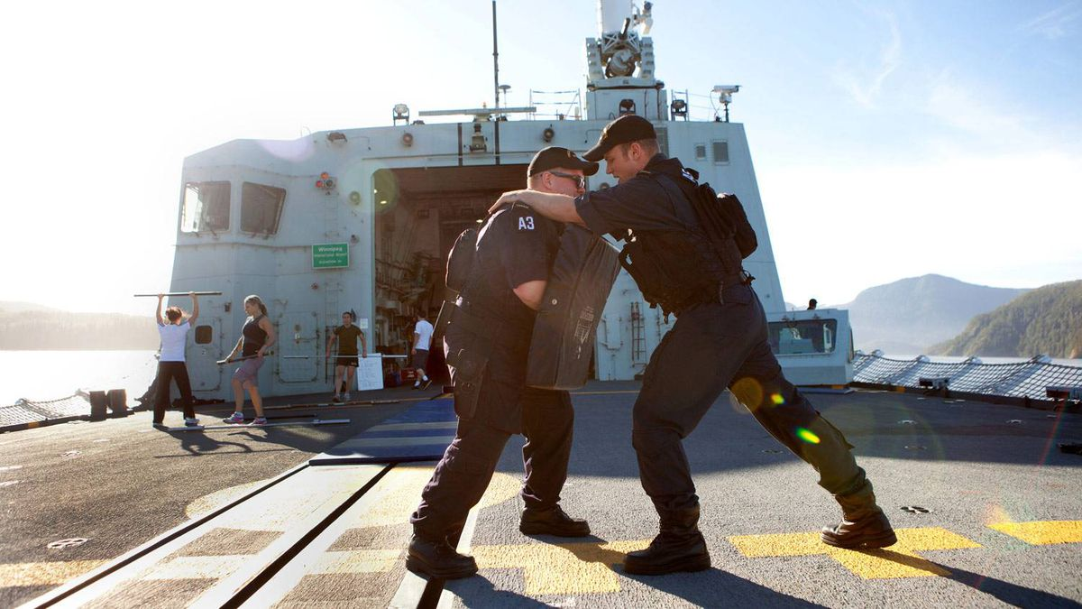 Sub-Lieutenant Dave Hendry and Able Seaman Shawn Martin give a naval boarding party technique demonstration on the flight deck of HMCS Winnipeg.