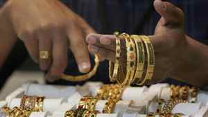 A saleswoman at a store in Bangalore shows off gold jewellery.