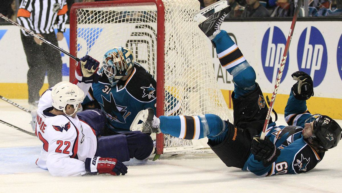 Washington Capitals right wing Mike Knuble (22) collides with San Jose Sharks defenseman Jason Demers (60) in front of goalie Antti Niemi (31), of Finland, during the first period of an NHL hockey game in San Jose, Calif., Saturday, Jan. 7, 2012. (AP Photo/Marcio Jose Sanchez)