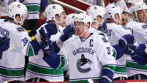 Henrik Sedin #33 of the Vancouver Canucks celebrates with teammates on the bench after scoring a second period goal against the Phoenix Coyotes during the NHL game at Jobing.com Arena on March 8, 2011 in Glendale, Arizona.