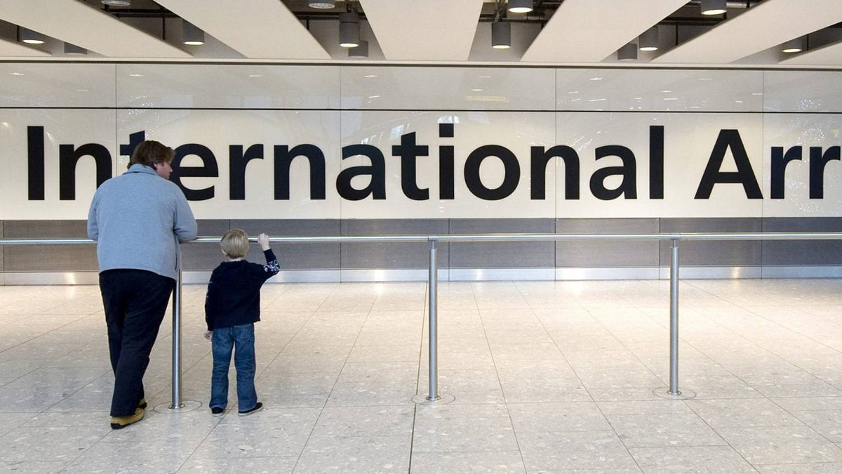 A father and son wait for a relative at Terminal 5's arrivals area at Heathrow Airport, London, Wednesday, Nov. 30, 2011.