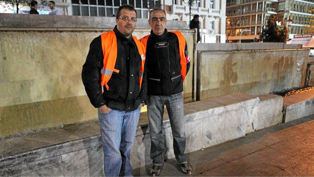 """Theodoros Marinelis, 42, owns an advertising agency; his friend Charis Lekkas, 45, is unemployed. They wear reflective vests as part of a volunteer security detail for medical workers at an anti-government rally; such events have turned violent, even deadly, in recent months. Mr. Marinelis has laid off all but one of his nine employees, as business slumped 70 per cent in the last year. None of his former workers have found new jobs, he said, but the hardship has not seriously affected his lifestyle. He was forced to sell his Audi A3, but still drives his motorcycle and his wife's Audi A6. """"We can afford only the basics,"""" he said, without irony."""