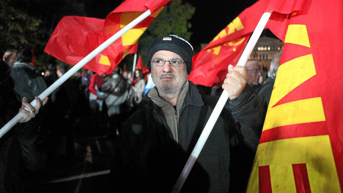 """Yanis Tsakalos, 51, carries a Communist flag at a rally in front of the Greek Parliament on Friday night. His wife lost her job as a sales clerk five days ago, he said, and his own work as a street sweeper seems increasingly at risk because of downsizing by the municipal government. His salary has been cut in half in the last two years, he said, and he can no longer afford to buy fuel for the central heating system in their home. """"We get under a pile of blankets and use the fireplace,"""" he said."""