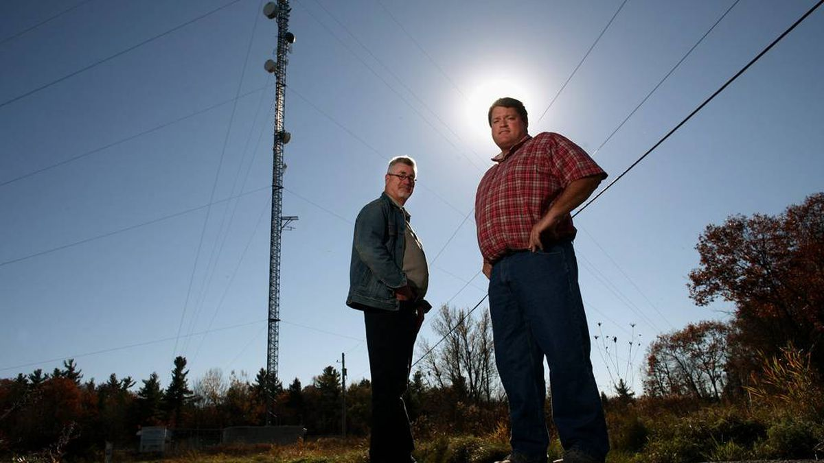 RipNet CEO Kingsley Grant (right) and CFO Eric Rothschild stand next to one of the company's wireless tower near Brockville, Ont.