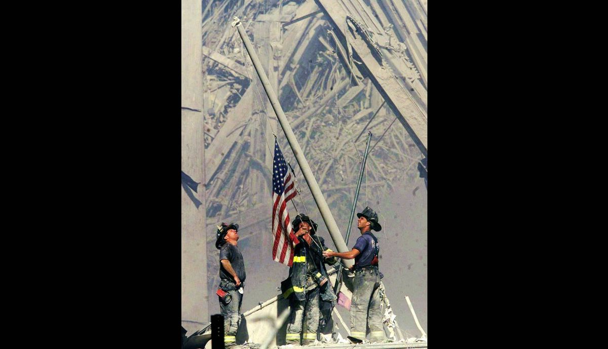 Firefighters raise a flag late in the afternoon on Sept. 11, 2001, in the wreckage of the World Trade Center towers in New York. From left: George Johnson, Dan McWilliams and Billy Eisengrein.